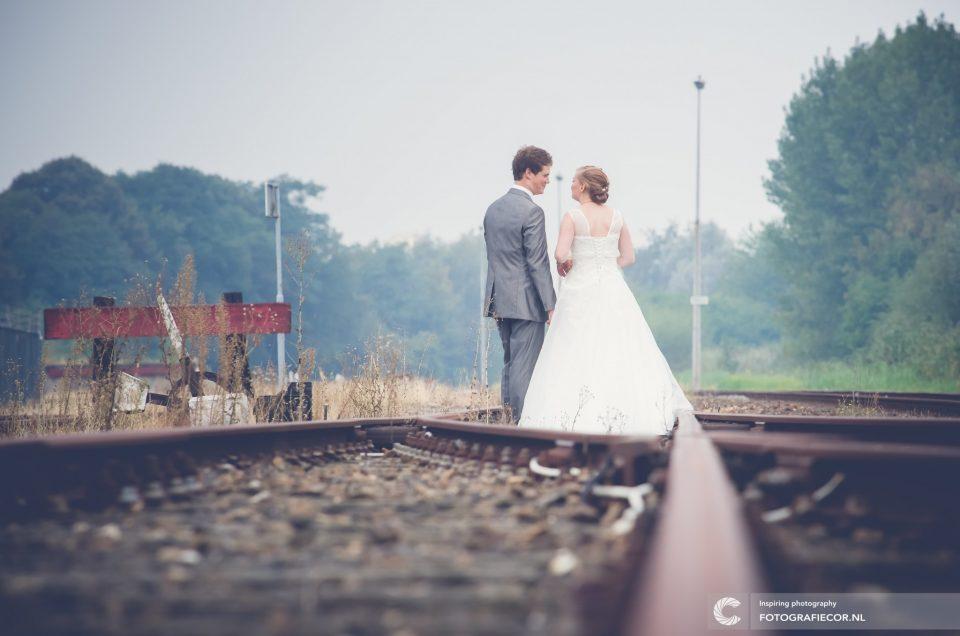 Trouwfoto's | Bruidspaar loopt op oude spoorlijn | industriële look