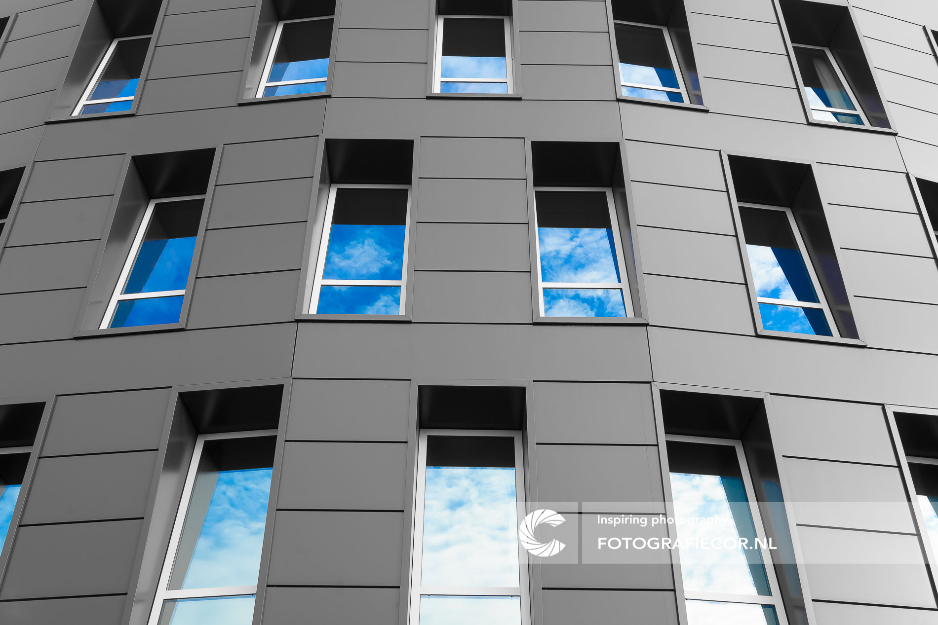 Bewolkte hemel en glas gebouw | architectuurfotograaf