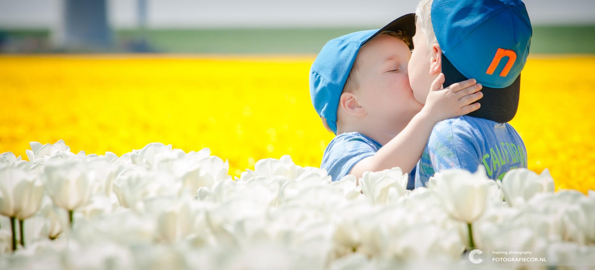 Gezinsfoto laten maken tussen de tulpenvelden van kinderen | familiefoto buiten fotograaf Kampen Zwolle Emmeloord