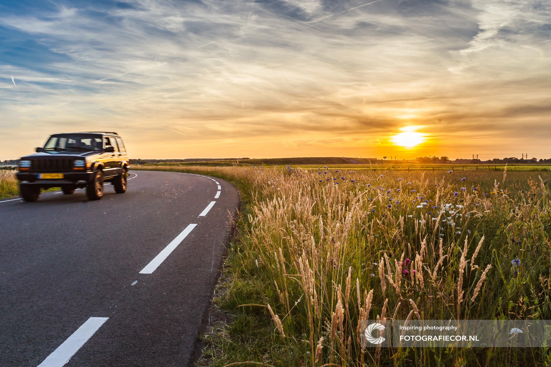 Auto rijdt tussen de weiland tijdens zonsondergang | Kampen | landschap | bypass