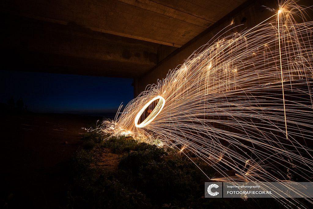 Spetterende brandende staalwol vonken onder een viaduct