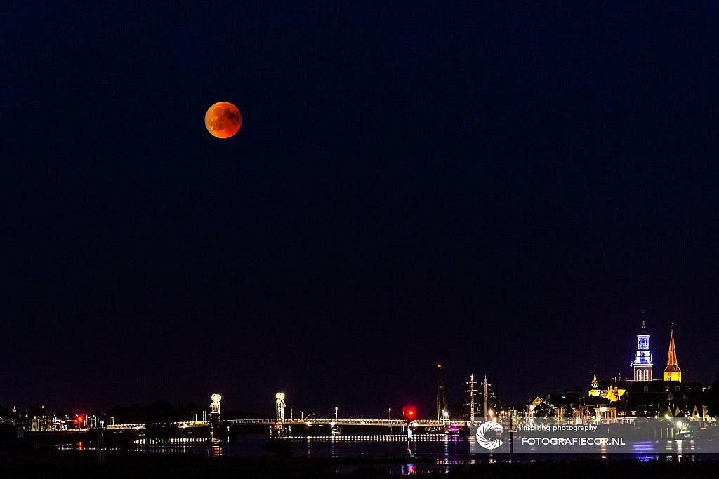Bloedmaan boven verlichte stadsomgeving en Nederlandse rivier de IJssell